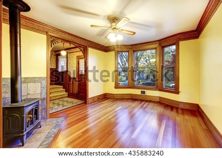 Unfurnished living room with fireplace, hardwood floor and pastel yellow walls - stock photo