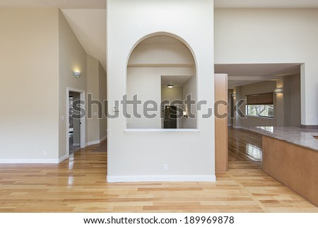 Unfurnished living room with wooden flooring, arch,facing hallway - stock photo