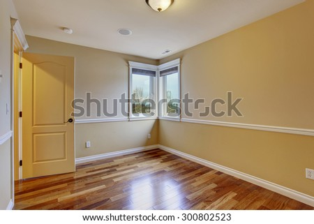 Unfurnished room with hardwood floor and yellow walls.