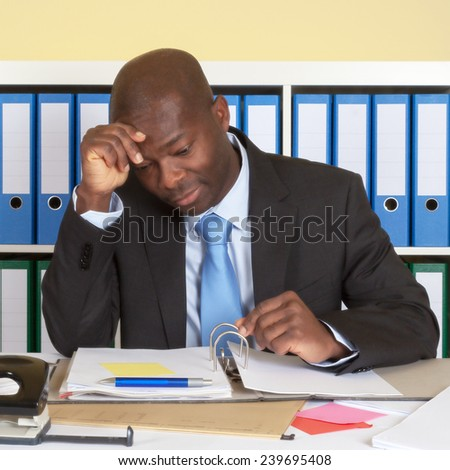 Unhappy african businessman at office - stock photo
