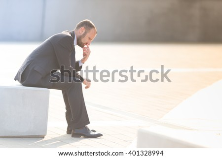 Unhappy and depressed businessman outdoor in the city