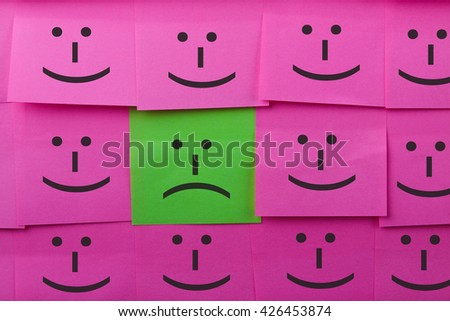 Unhappy and happy concept. Background of sticky notes. Green sticky note is among pink sticky notes. - stock photo