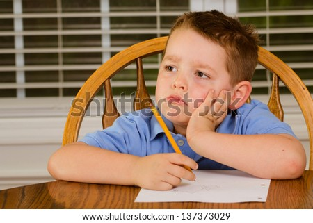 Unhappy and rebellious child doing his homework at kitchen table at home