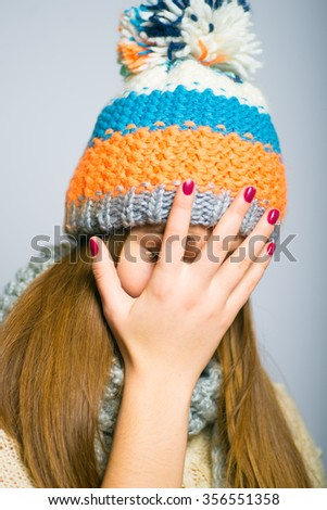 unhappy beautiful girl covers her face with her hands, knit cap, winter concept, photo studio, portrait of a woman isolated on gray background - stock photo