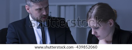 Unhappy boss looks at his intimidated female worker