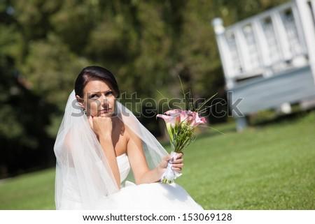 Unhappy bride with a wedding bouquet - stock photo