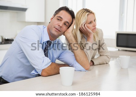 Unhappy business couple not talking after an argument in the kitchen at home - stock photo