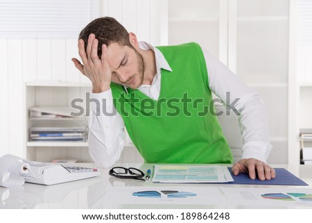 Unhappy businessman sitting concerned and frustrated in the office. - stock photo