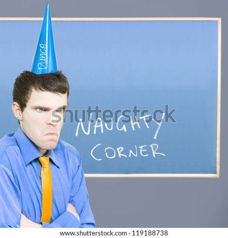 Unhappy Businessman Sulking In The Naughty Corner While Wearing A Dunce Hat In A Depiction Of A Bad Business Decision - stock photo