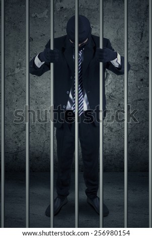 Unhappy businessman with mask standing inside the jail as the prisoner - stock photo