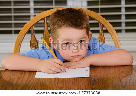 Unhappy child doing his homework at kitchen table at home - stock photo