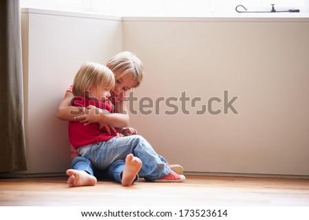 Unhappy Children Sitting On Floor In Corner At Home - stock photo