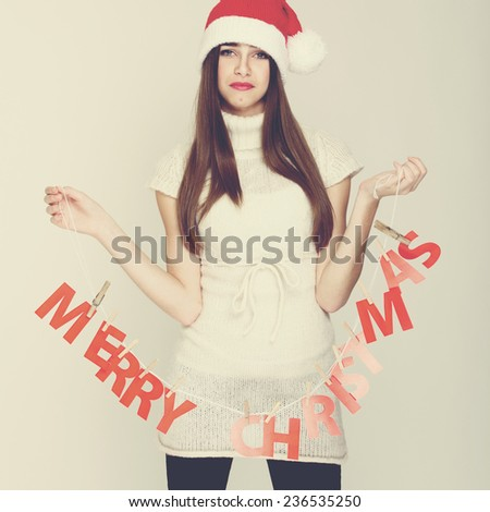 Unhappy Christmas woman with Merry Christmas sign. Closeup studio shot of pretty teenage girl with hanging decoration. Square format, instagram filter. - stock photo