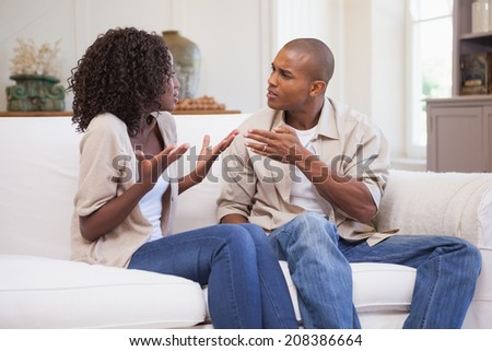 Unhappy couple arguing on the couch at home in the living room - stock photo