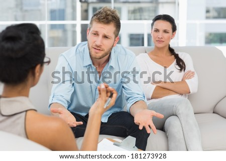Unhappy couple at therapy session with man talking to therapist in therapists office - stock photo