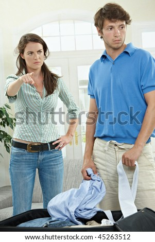 Unhappy couple fighting. Woman pointing out, man packing his clothes. - stock photo