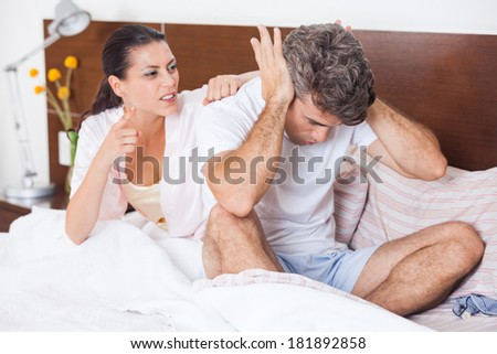 unhappy couple in a bed, having conflict problem cheat separate, aggressive woman scream on man, upset sad negative emotions concept - stock photo