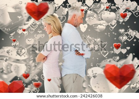 Unhappy couple not speaking to each other against grey valentines heart pattern - stock photo