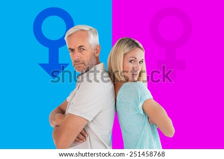 Unhappy couple not speaking to each other against pink and blue - stock photo