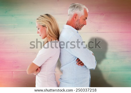 Unhappy couple not speaking to each other against pink and green planks - stock photo