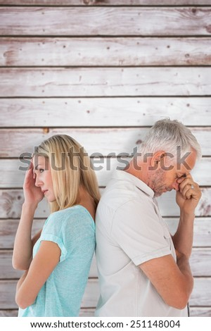 Unhappy couple not speaking to each other against wooden planks - stock photo