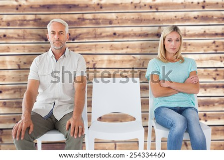 Unhappy couple not speaking to each other against wooden planks background - stock photo