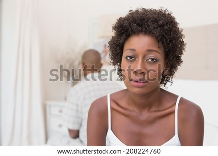 Unhappy couple not speaking to each other on bed at home in the bedroom - stock photo