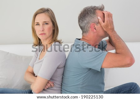 Unhappy couple not talking after an argument in the living room at home - stock photo