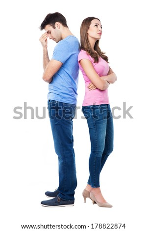 Unhappy couple standing back to back - stock photo