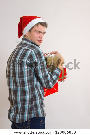 Unhappy disappointed greedy young man - Santa Claus holding gift boxes - stock photo