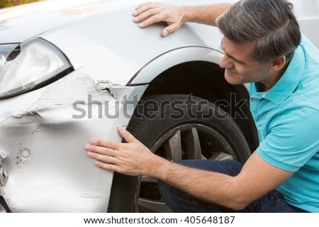 Unhappy Driver Inspecting Damage After Car Accident
