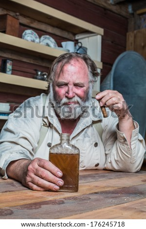Unhappy Drunk Cigar Smoking Western Man Looks Towards His Drink as he Sits at Table - stock photo