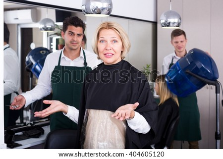 Unhappy female pensioner having fight with hairdresser in salon. Focus on the woman - stock photo