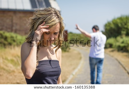 Unhappy frustrated woman in focus and angry man leaving on the background after quarrel - stock photo