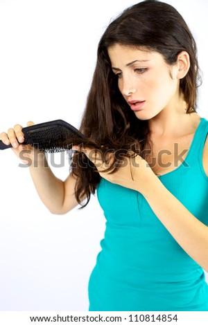 Unhappy girl about her bad long hair brushing - stock photo