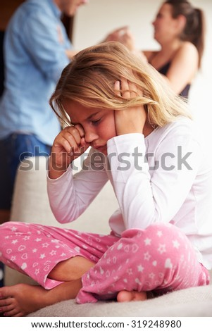 Unhappy Girl At Home With Parents Arguing In Background - stock photo