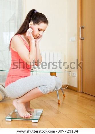 unhappy girl standing on bathroom scales at home interior