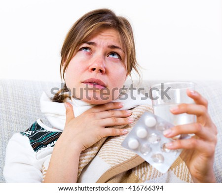 Unhappy girl suffering of sore throat and fever at home - stock photo