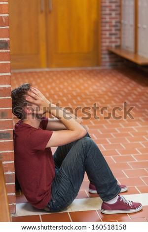 Unhappy handsome student covering his face in school - stock photo