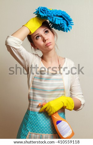 Unhappy housewife. A young woman stands with a rag in his hand after a serious cleaning. The concept of household chores a burden - stock photo