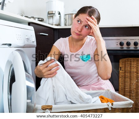 Unhappy housewife with dirty white shirt near washing machine