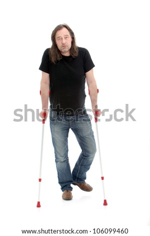 Unhappy injured or disabled middle-aged man walking with the aid of crutches - stock photo