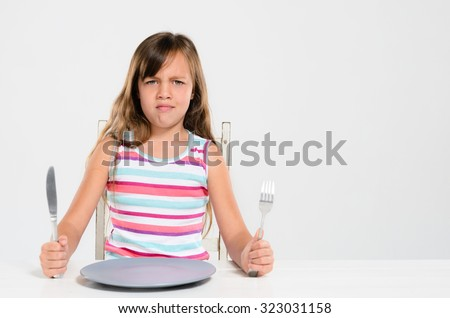 Unhappy kid at table, throwing a tantrum, bad table manners - stock photo