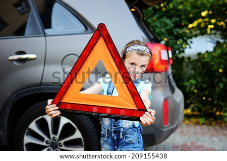 Unhappy kid girl holds red warning triangle on the family car background - stock photo