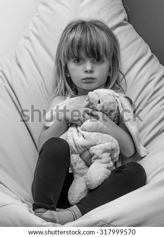 Unhappy little girl cuddling a toy rabbit.