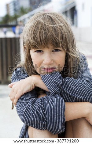 Unhappy little girl wearing striped t-shirt of her father, sitting on the bench. Problems with parents - stock photo