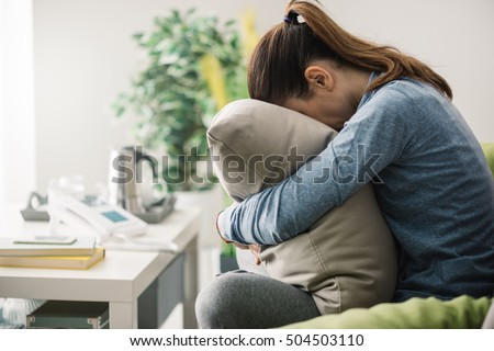 Unhappy lonely depressed woman at home, she is sitting on the couch and hiding her face on a pillow, depression concept