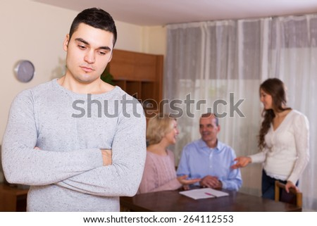 Unhappy man faced with misunderstanding big european family