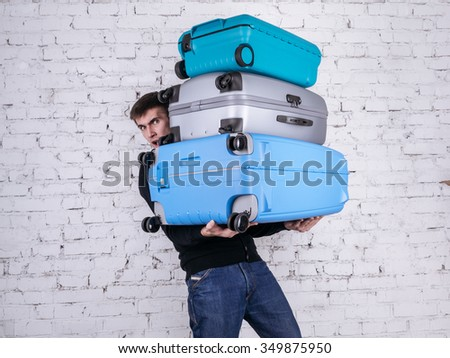 Unhappy man holding three heavy suitcases in hand. Travel light. - stock photo