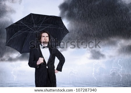 Unhappy Man Holding Umbrella in a Rain Storm and Frowning - stock photo